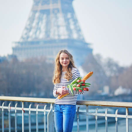 Beautiful young girl with fresh tasty traditional French bread (baguette) and tulips near the Eiffel tower Stock Photo