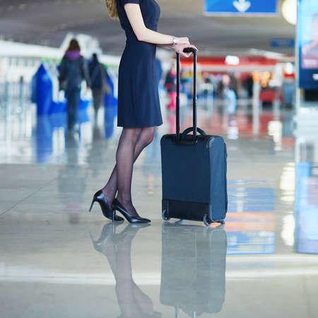 Mooie vrouwelijke passagier of steward in internationale luchthaven met handbagage Stockfoto