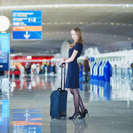 Beautiful female passenger or flight attendant in international airport with hand luggage