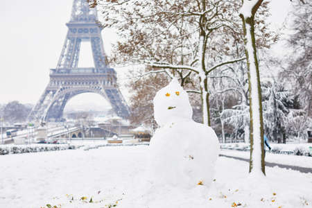 Funny snowman and the Eiffel tower on a day with heavy snow. Unusual weather conditions in Paris