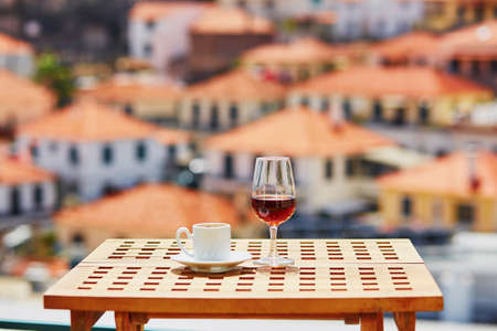 Glasse of Madeira wine and cup of fresh espresso coffee in street cafe with view to Funchal town, Madeira, Portugal