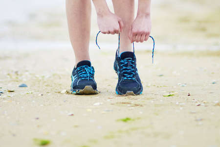 Young jogger tying sport running shoes laces. Fitness and healthy lifestyle concept Stockfoto