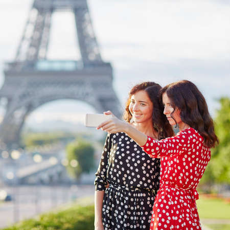 Beautiful twin sisters taking selfie in front of Eiffel Tower while traveling in Paris, France. Happy smiling girls enjoy their vacation in Europe 写真素材 - 95221234