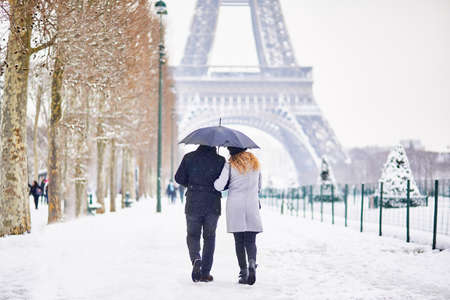 Couple of tourists walking in Paris under umbrella on a day with heavy snow. Unusual weather conditions in Paris Foto de archivo