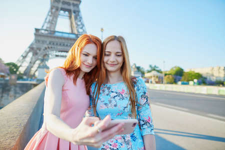 Two friends taking selfie near the Eiffel tower in Paris, France 写真素材 - 96031344