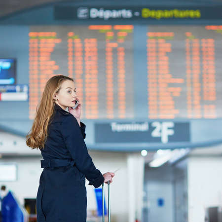 Young woman in international airport near large information display Stock fotó - 97312836
