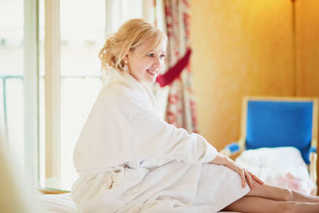 Beautiful young woman in white bathrobe sitting on bed at early morning and stretching after night sleep