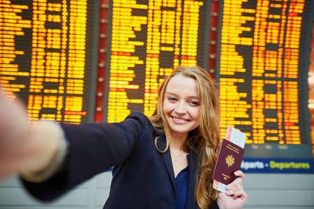 Young woman in international airport near large information display taking selfie Reklamní fotografie - 97387595