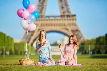 Two beautiful young women having picnic near the eiffel tower in Paris, France