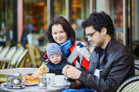 Happy family of three in Parisian outdoor cafe. Mother, father and their little son drinking coffee and eating croissants in a restaurant in France Stock Photo