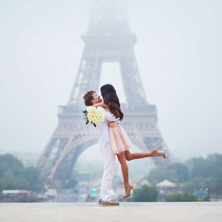 Beautiful romantic couple in love with bunch of white roses near the Eiffel tower in Paris on a cloudy and foggy rainy day Stock Photo
