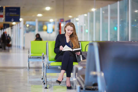 Young woman in international airport reading a book while waiting for her flight 版權商用圖片