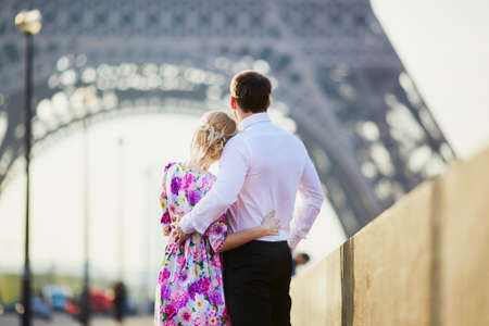Romantic couple together in Paris kissing near the Eiffel tower Imagens