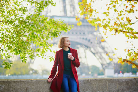 Beautiful young French woman drinking coffee near the Eiffel tower in Paris on a fall or spring day