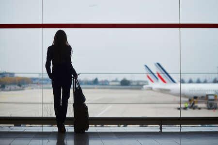 窓から飛行機を見ている国際空港の若い女性 写真素材 - 97387631