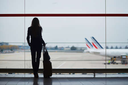 Young woman in international airport looking at planes through the window
