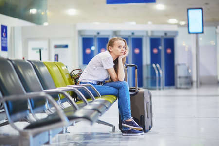 Young woman in international airport waiting for her flight