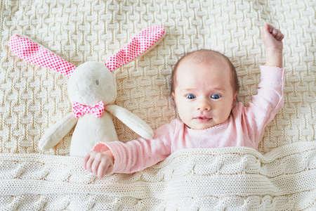 Bambina di un mese sdraiata a letto sotto la coperta lavorata a maglia insieme al suo giocattolo, coniglietto di peluche rosa Archivio Fotografico - 99609428