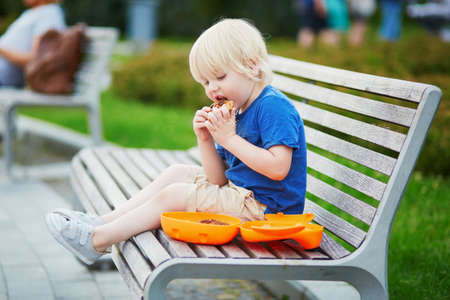 Adorable little boy sitting on the bench with lunchbox in park. Healthy food and snacks for kids. Child eating his breakfast or lunch outdoors