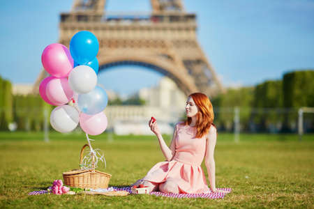 Beautiful young woman in pink dress with bunch of balloons having picnic near the Eiffel tower in Paris, France