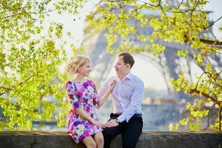Beautiful romantic couple at the Eiffel tower on a spring day in Paris, France. Tourism and vacation concept