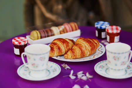 Traditional French croissants, macaroons and two cups of coffee in Parisian outdoor cafe