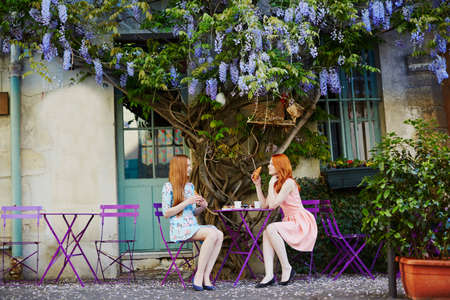 Two Parisian women drinking coffee together in an outdoor cafe with wisteria in full bloom. Paris, France Banque d'images