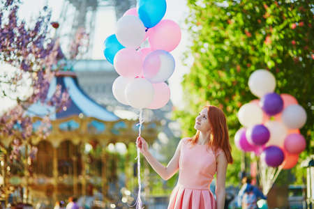 Happy young girl with bunch of pink and blue balloons in front of the Eiffel tower and merry-go-round in Paris, France