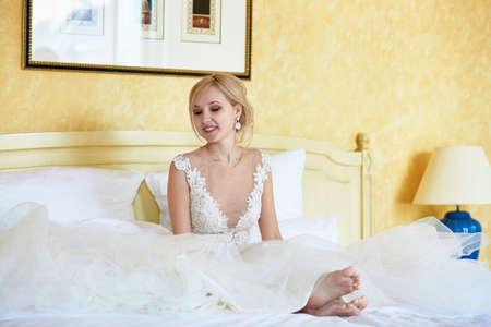 Vrolijke jonge bruid in huwelijkskleding die op bruidegom wachten om te komen en van de ochtend van haar speciale dag thuis of in hotelruimte genieten