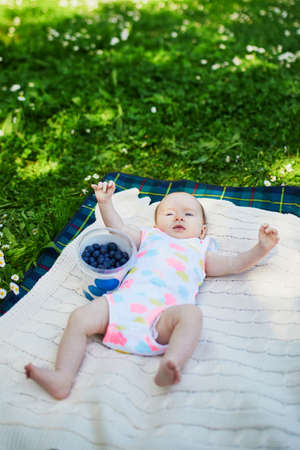 Adorable baby girl lying on the grass on a summer day. Family activities with kids. Summer picnic with a child Stock Photo