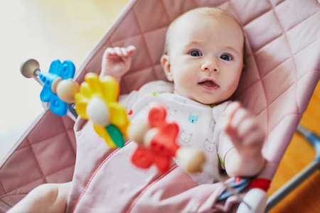 Adorable baby girl sitting in bouncer and playing with colorful toys Stockfoto