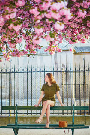 Beautiful French woman walking in Paris on a spring day at cherry blossom season Stock Photo