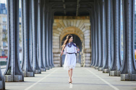 Young French woman in white dress on Bir-Hakeim bridge in Paris, France