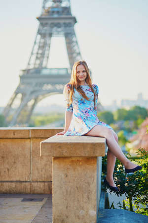 Beautiful young girl in blue dress near the Eiffel tower, enjoying her time in Paris, France