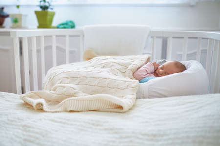 Newborn baby girl having a nap in co-sleeper crib attached to parents bed