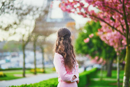 Happy young woman in pink dress enjoying cherry blossom season in Paris, France