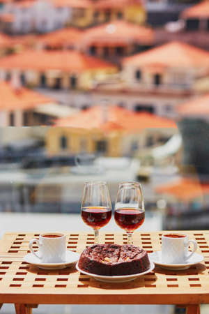 Two glasses of Madeira wine, two cups of fresh espresso coffee and traditional Portuguese honey and nut dessert bolo de mel in cafe with view to Funchal town, Madeira, Portugal