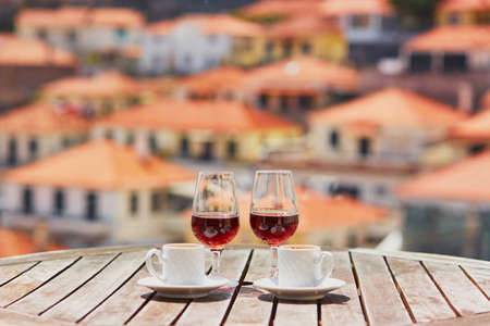 Two glasses of Madeira wine and two cups of fresh espresso coffee in street cafe with view to Funchal town, Madeira, Portugal Stock Photo