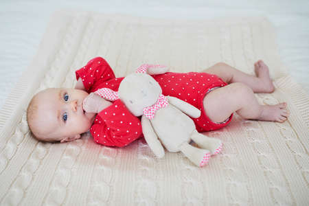 Baby girl holding stuffed bunny. Comfort object for infant. Newborn with favorite toy