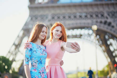 Two friends taking selfie near the Eiffel tower in Paris, France