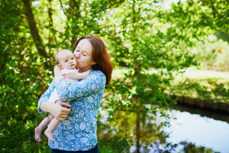 Mother holding her 2 months old baby girl and kissing her Stock Photo - 102459520