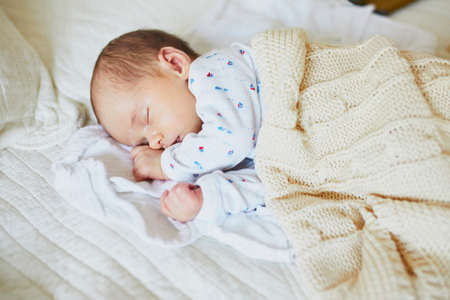 1 month old baby girl sleeping under knitted blanket. Child having a day nap in parents bed
