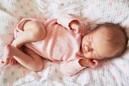 Newborn baby girl sleeping in her crib. Infant having day nap Stock Photo