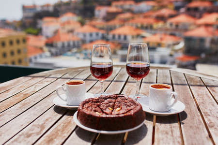 Two glasses of Madeira wine, two cups of fresh espresso coffee and traditional Portuguese honey and nut dessert bolo de mel in cafe with view to Funchal town, Madeira, Portugal Banco de Imagens - 102459634