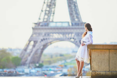 Happy young woman in white dress near the Eiffel tower in Paris, France