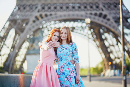 Two friends taking selfie near the Eiffel tower in Paris, France 写真素材 - 102459782