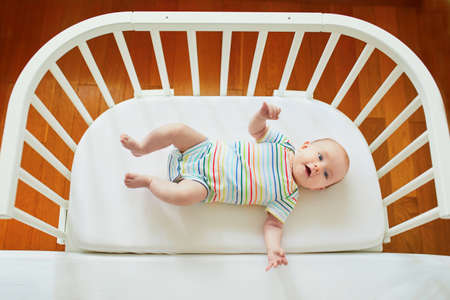 Baby girl lying in co-sleeper attached to parents bed Stock Photo