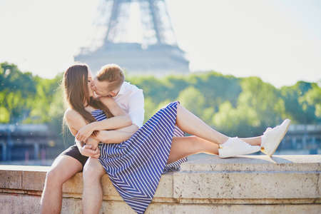 Romantic couple together in Paris kissing near the Eiffel tower Stock Photo