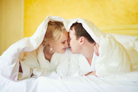 Happy young couple in white bathrobes drinking coffee together in bed at morning