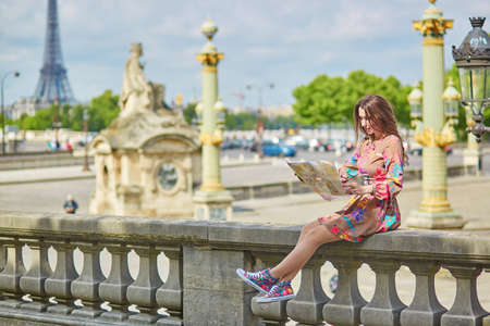 Young beautiful and elegant Parisian woman sitting near the Eiffel tower in Paris Фото со стока